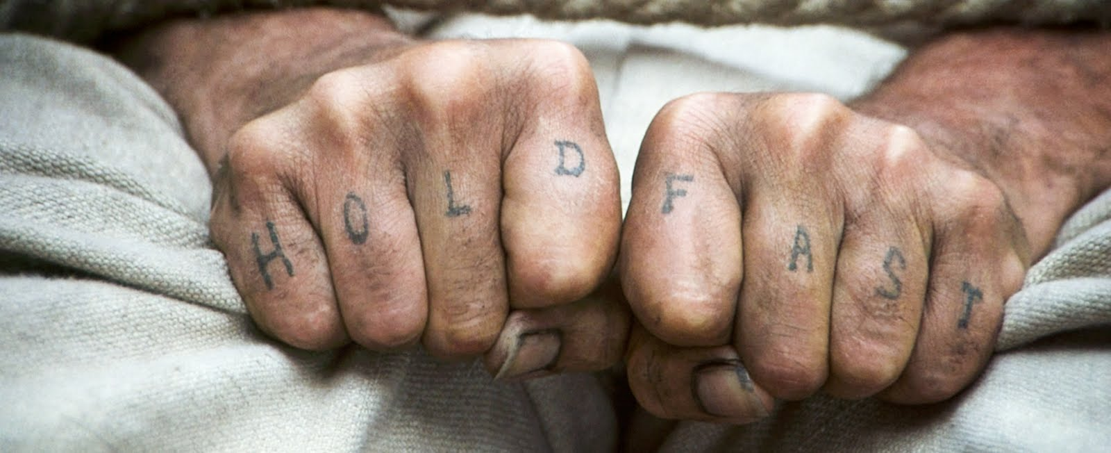 "Two fists held close together. On each knuckle a letter is tattooed. The words ""Hold Fast"" are spelled out across them."