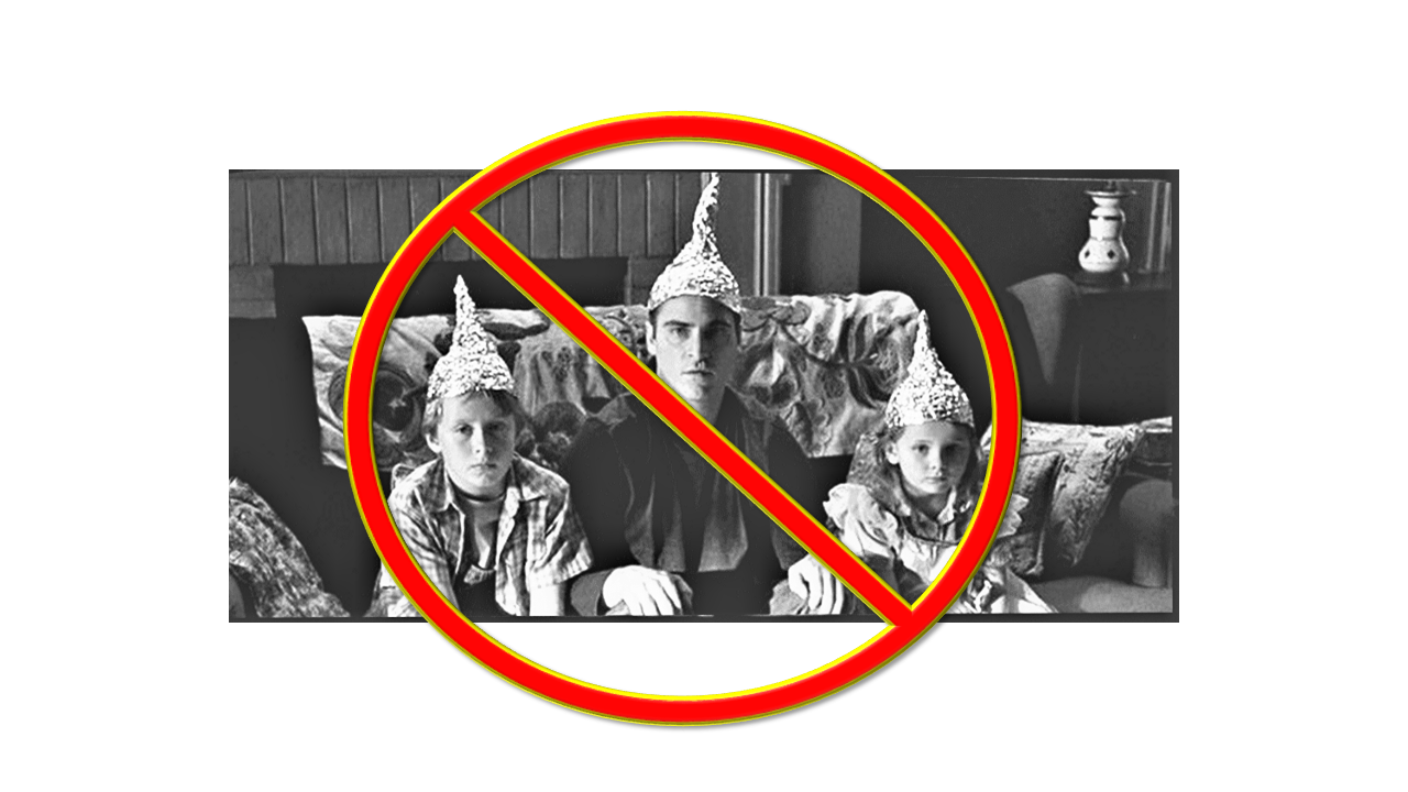 Three people sitting on a couch wearing homemade aluminum foil hats.
