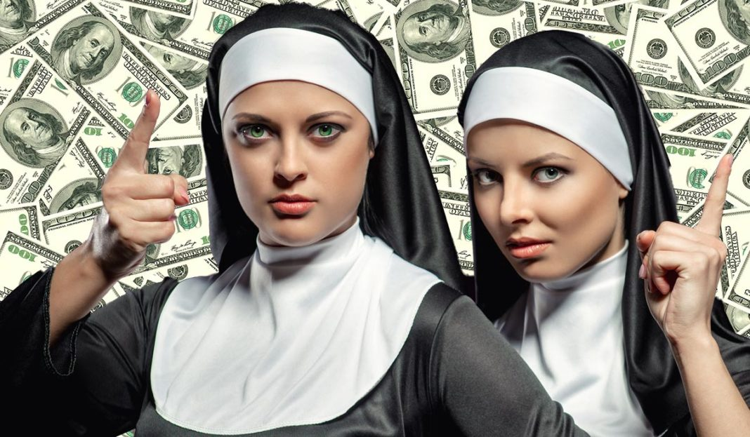 Two women dressed in nun costumes posing in front of a background image of $100 bills.