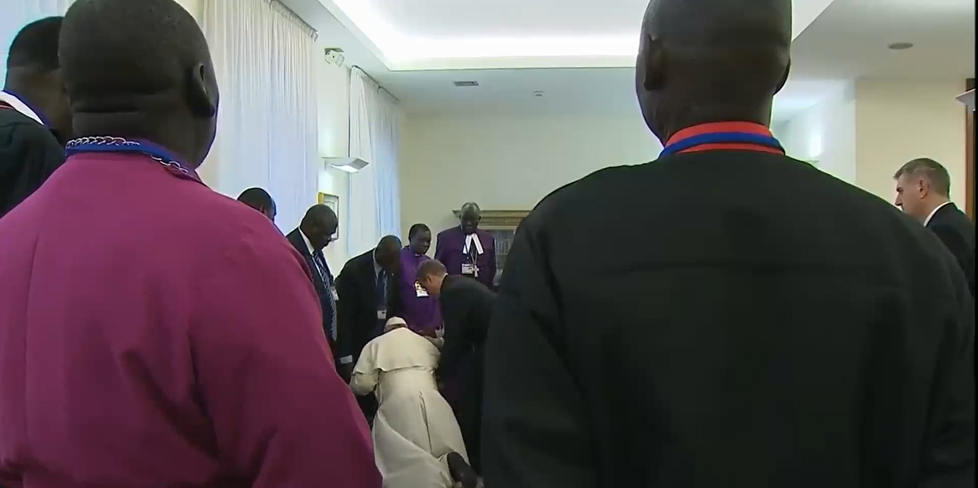 Pope Francis kisses the feet of a Sudanese peace delegate as a crowd looks on.