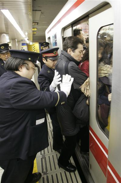 Station workers push a passenger into a crowded subway train at the Ikebukuro station on the Marunouchi line during rush hour in Tokyo